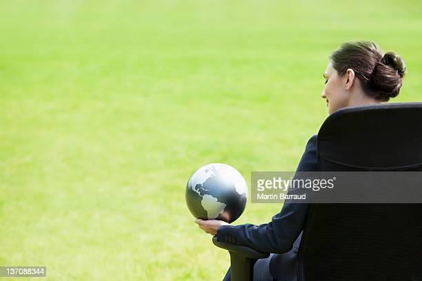 Businesswoman sitting outdoors holding globe