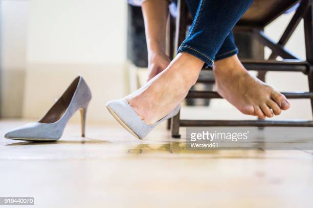businesswoman sitting taking off her high heels - talons hauts photos et images de collection