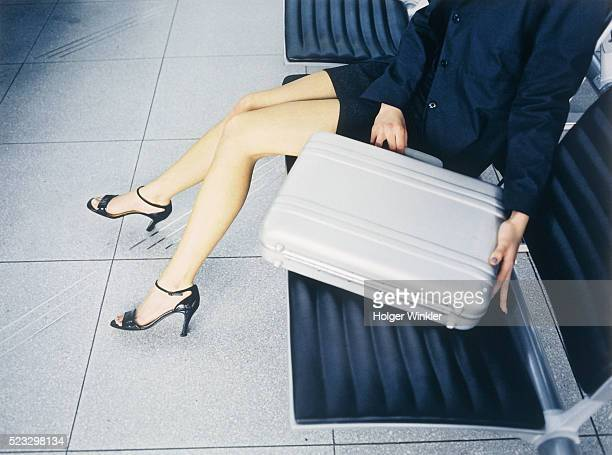 Businesswoman Sitting with Briefcase at Airport