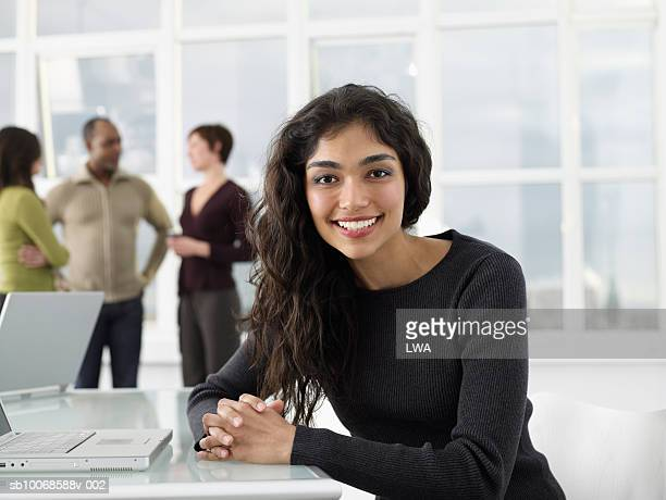 businesswoman sitting with laptop in office, smiling, portrait - afro caribbean ethnicity stock pictures, royalty-free photos & images