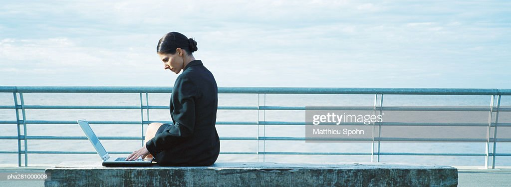 Businesswoman sitting with laptop, railing in background, panoramic : Stockfoto