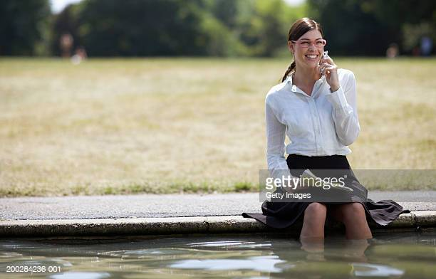 Businesswoman sitting with legs in pond, using mobile phone, smiling