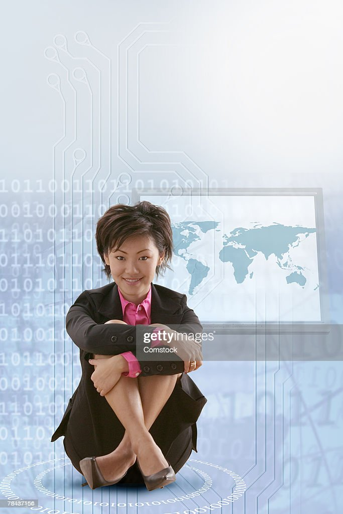 Businesswoman sitting with world map behind her : Stockfoto