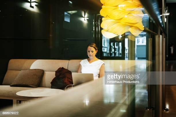 Businesswoman Sitting Working On Laptop In Hotel Bar