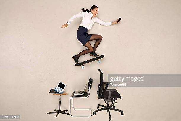 Businesswoman skateboarding over office chairs with smartphone