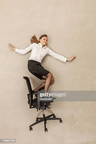 Businesswoman skating on office chair