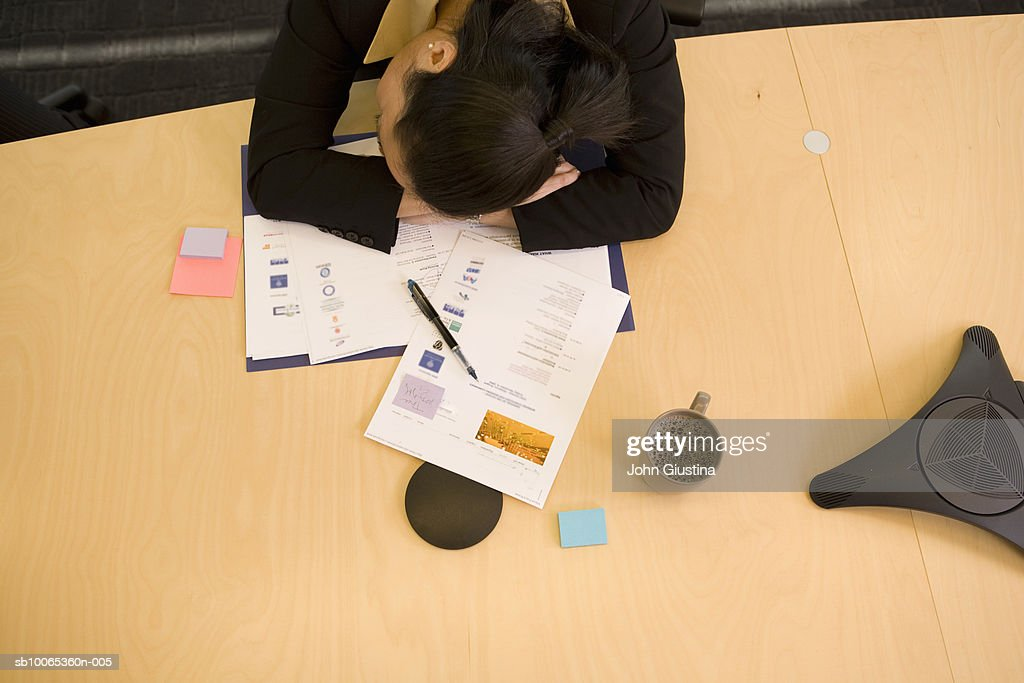 Businesswoman sleeping at desk in conference room, elevated view : Foto stock