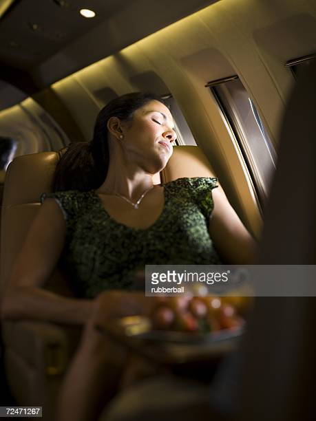 A businesswoman sleeping on an airplane
