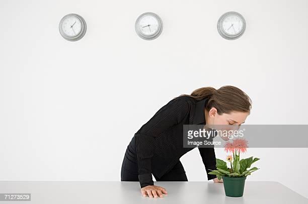 Businesswoman smelling a flower