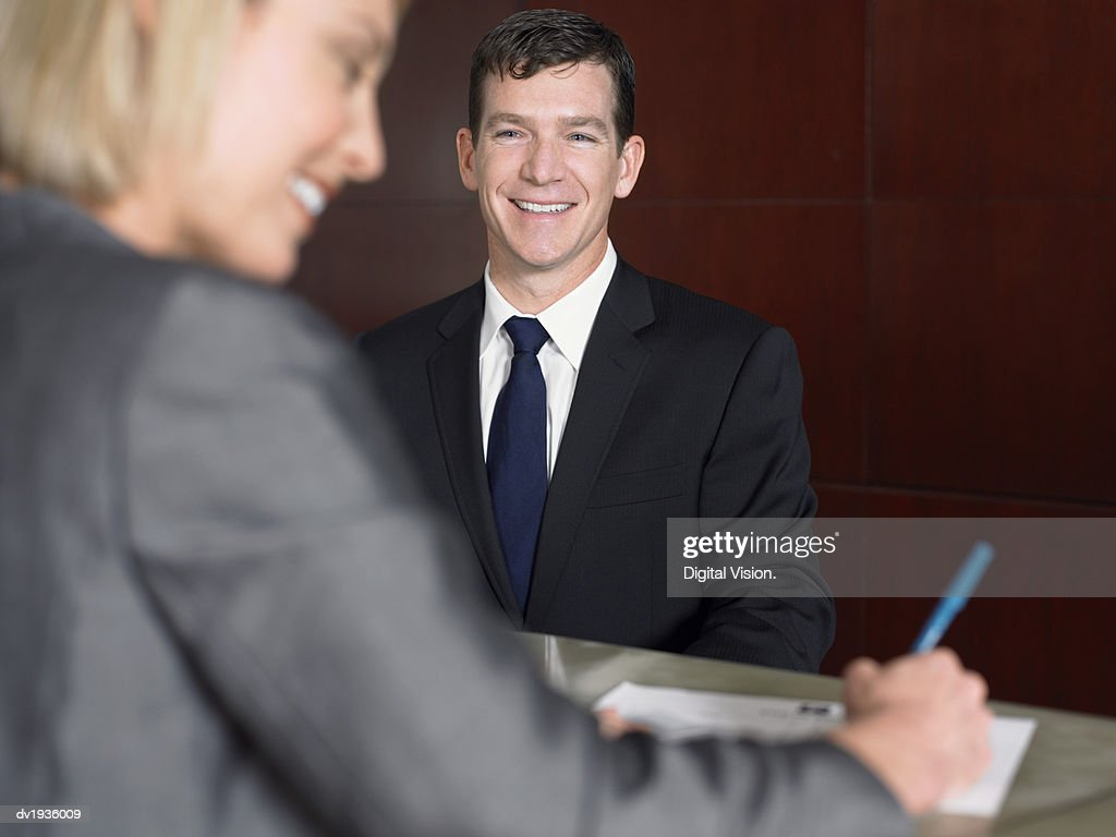Businesswoman Smiles as She Signs a Document at a Reception Desk : Stock Photo