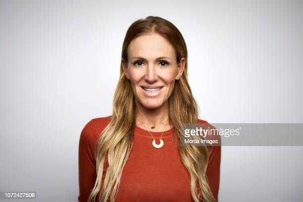 businesswoman smiling against white background - femmes d'âge moyen photos et images de collection