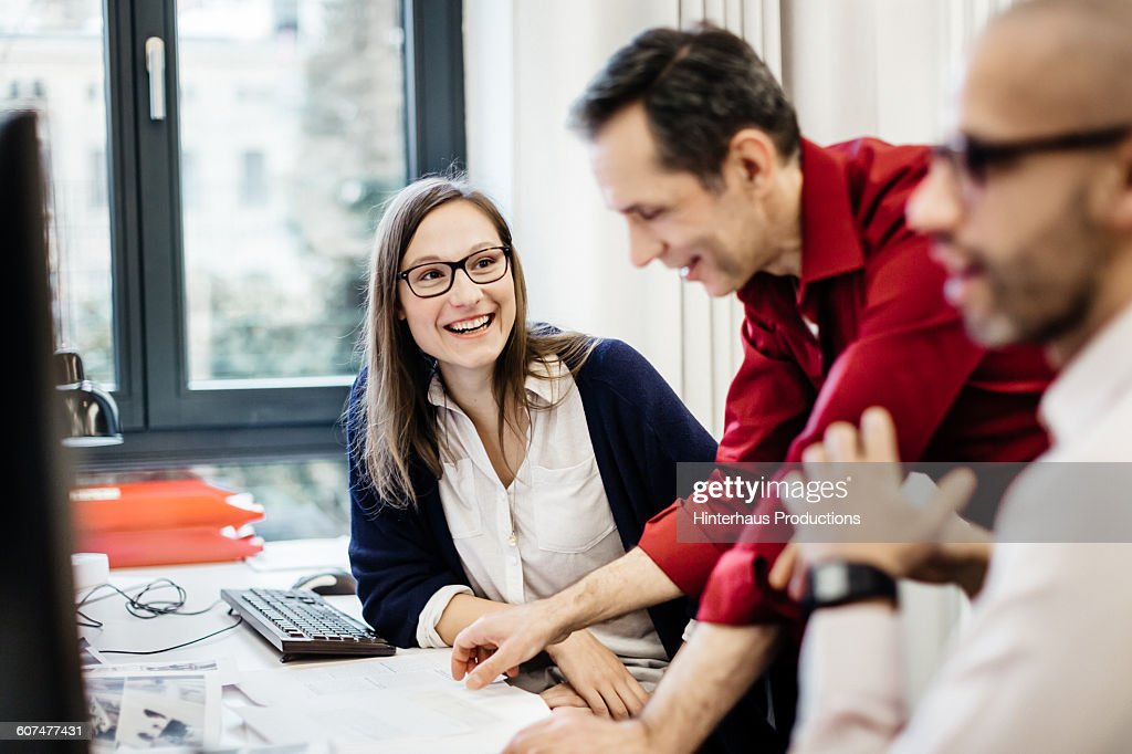 Businesswoman smiling at colleague in office : Stock Photo