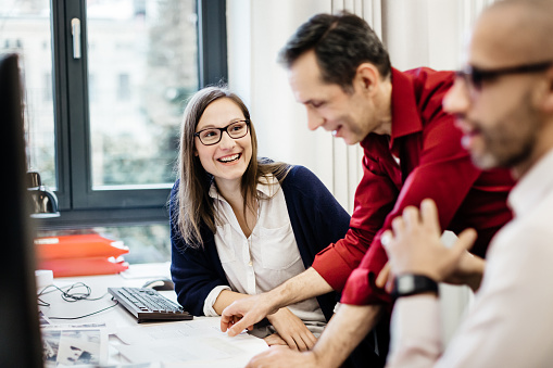 Businesswoman smiling at colleague in office - gettyimageskorea
