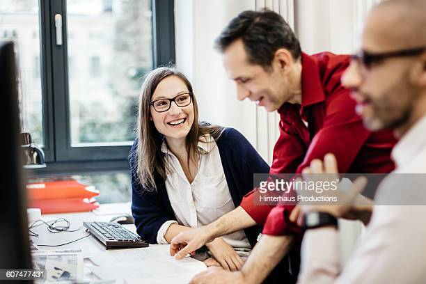businesswoman smiling at colleague in office - central europe stock photos and pictures