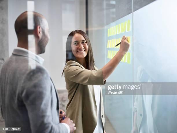 businesswoman smiling at colleague writing on sticky notes at glass pane in office - werkstatt stock-fotos und bilder