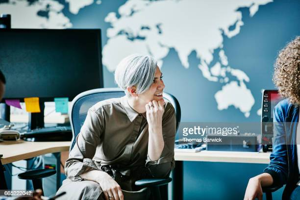 Businesswoman smiling during team meeting in high tech office