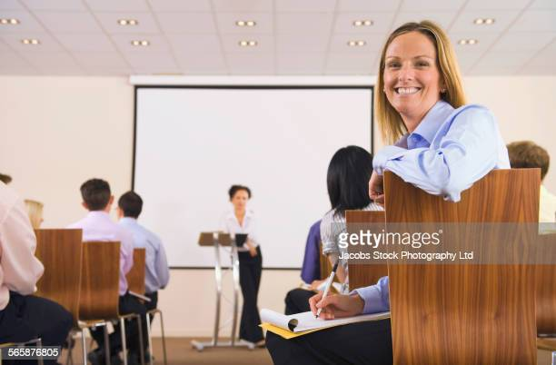 Businesswoman smiling in audience during presentation