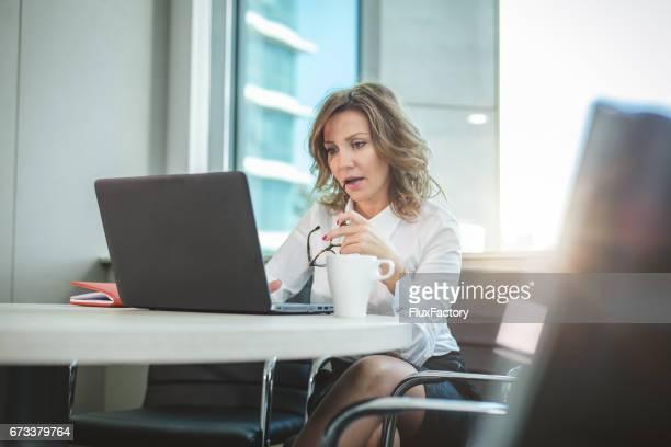 zakenvrouw glimlachend in haar kantoor en bijten bril