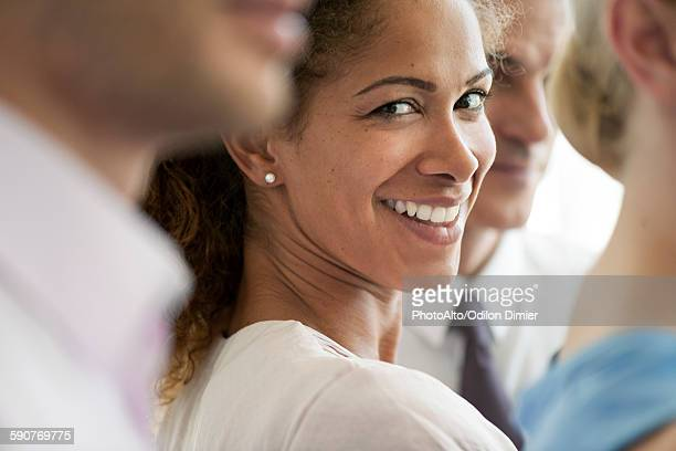 Businesswoman smiling over shoulder, portrait