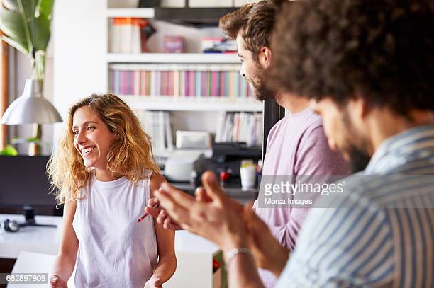 Businesswoman smiling while colleagues applauding