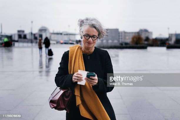 businesswoman smiling while texting on her lunch break - persona in secondo piano foto e immagini stock