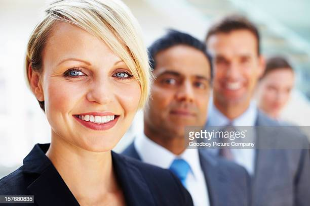Businesswoman smiling with her team in the background