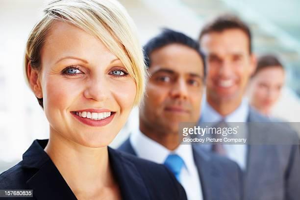 Lächelnde Geschäftsfrau mit ihrem team im Hintergrund