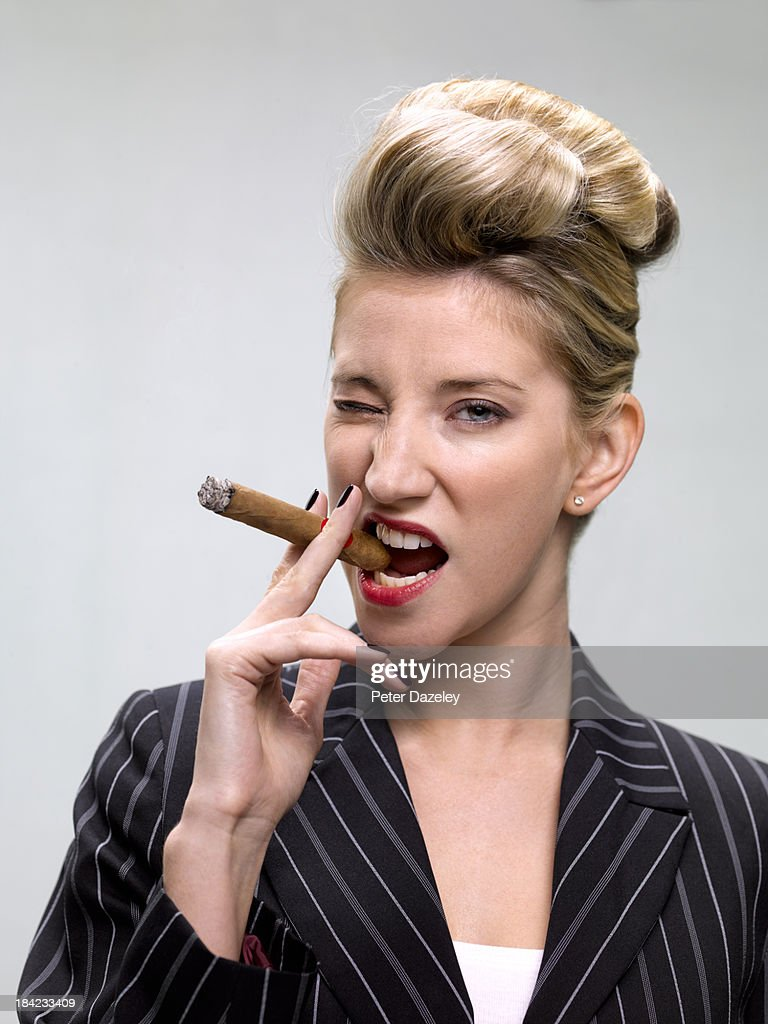 Businesswoman smoking cigar : Stock Photo