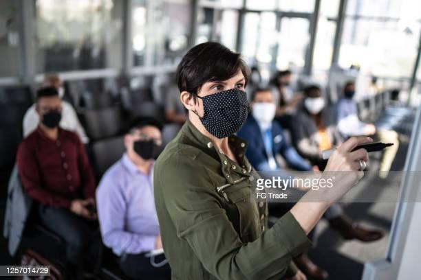 geschäftsfrau spricht auf einer geschäftskonferenz - mit gesichtsmaske - organised group stock-fotos und bilder