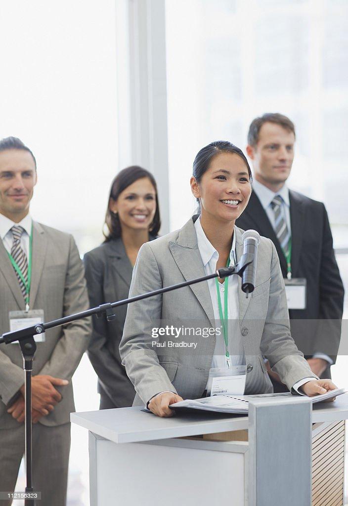 Mujer de negocios hablando en podium : Foto de stock