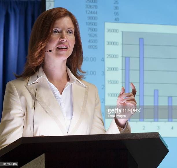 Businesswoman speaking at podium with graph in background