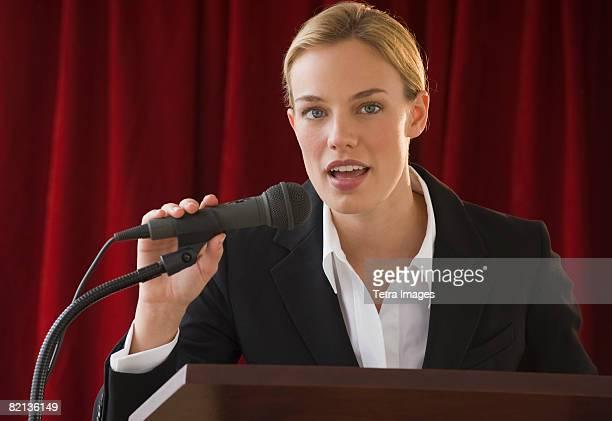 businesswoman speaking into microphone - homme politique photos et images de collection