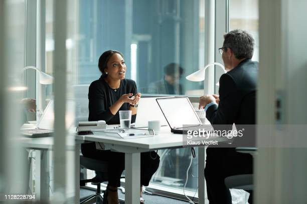 businesswoman speaking with co-worker in open office - zakenpersoon stockfoto's en -beelden