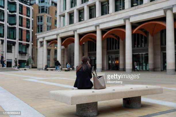 Businesswoman speaks on her mobile phone as she sits on a bench in Paternoster Square in the City of London, U.K., on Monday, Sept. 7, 2020. U.K....