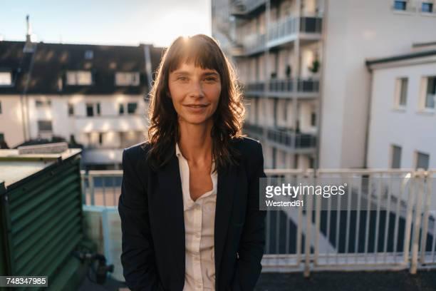 Businesswoman staanding on balcony enjoying the sunshine