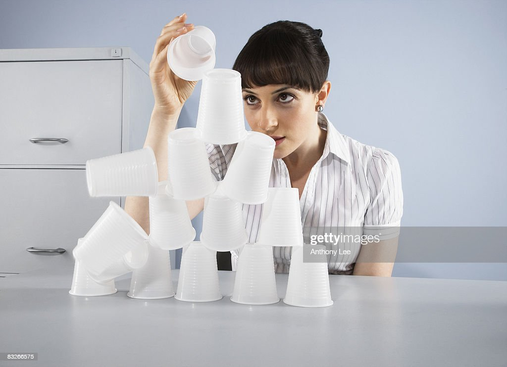 Businesswoman stacking plastic cups into pyramid : Stock Photo