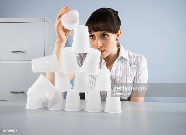 businesswoman stacking plastic cups into pyramid - wasting time stock pictures, royalty-free photos & images