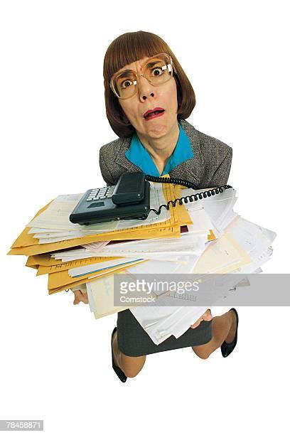 Businesswoman staggering under paperwork