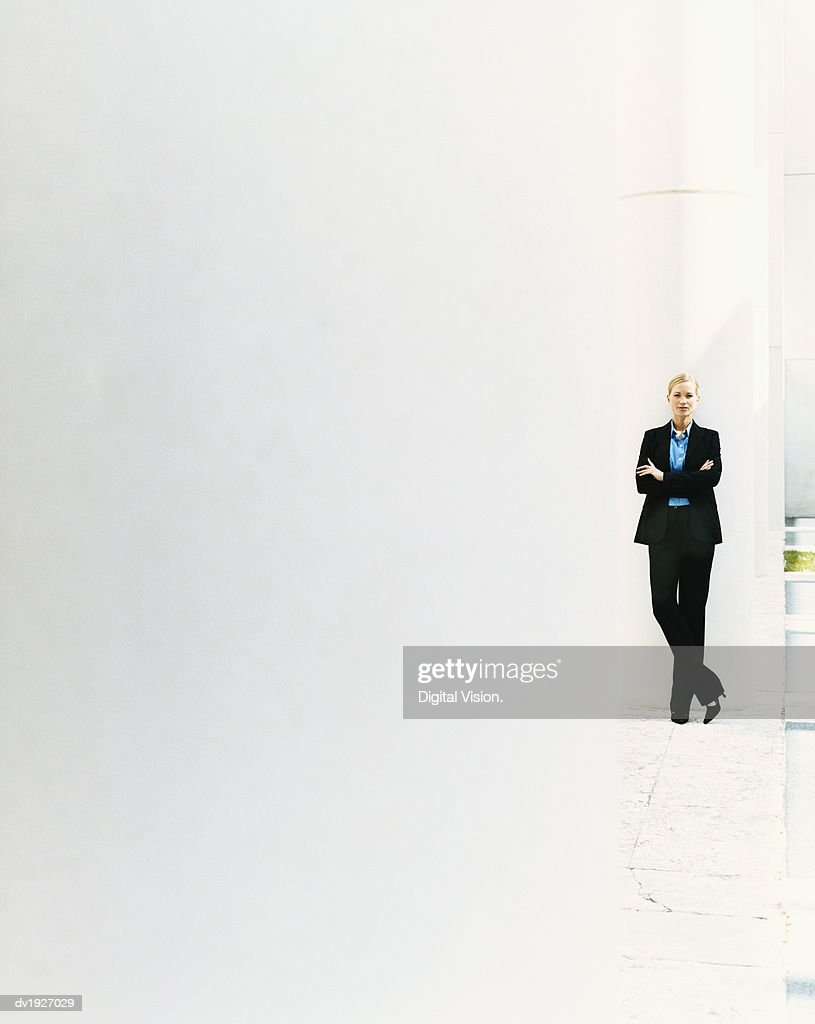 Businesswoman Standing Against a Column on the Outside of a Building : Stock Photo