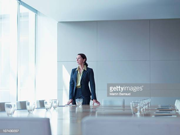 businesswoman standing alone in conference room - board room stock pictures, royalty-free photos & images