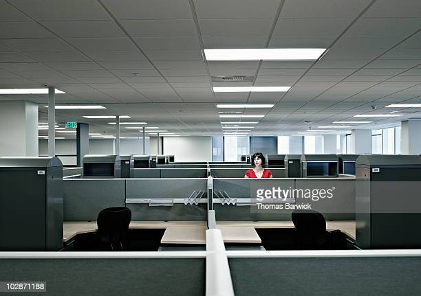 businesswoman standing alone in empty office - leer stock-fotos und bilder