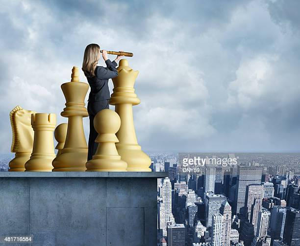Businesswoman standing among chess pieces looks through spyglass