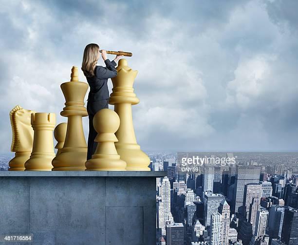Geschäftsfrau sieht in die Schachfiguren durch spyglass