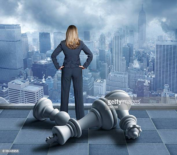 Businesswoman Standing Among Fallen Chess Pieces Looks Out Over City