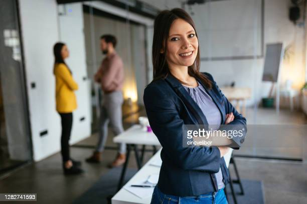 businesswoman standing and looking at camera - incidental people stock pictures, royalty-free photos & images