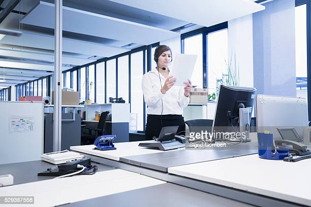 businesswoman standing and reading document in office, freiburg im breisgau, baden-w��rttemberg, germany - sigrid gombert stock pictures, royalty-free photos & images