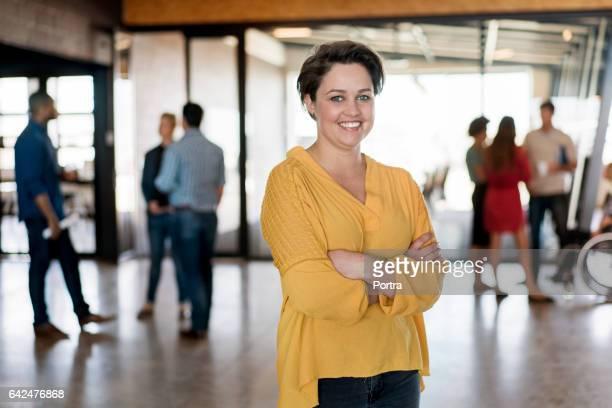 zakenvrouw staande armen gekruist in kantoor - onscherpe achtergrond stockfoto's en -beelden