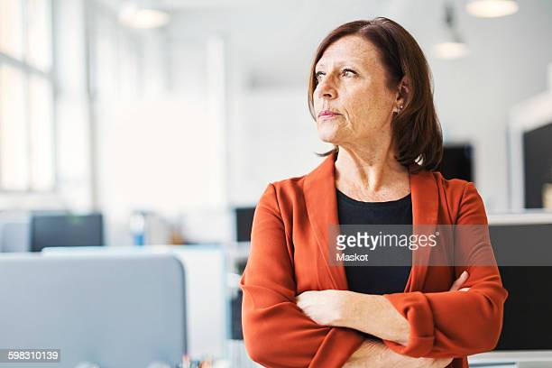 Businesswoman standing arms crossed while looking away in office