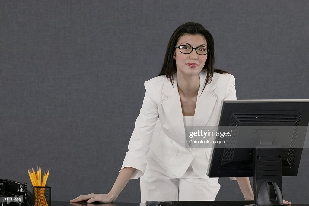 Businesswoman standing at desk : Stockfoto