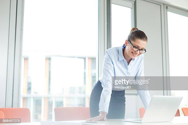 Businesswoman standing at desk reading emails